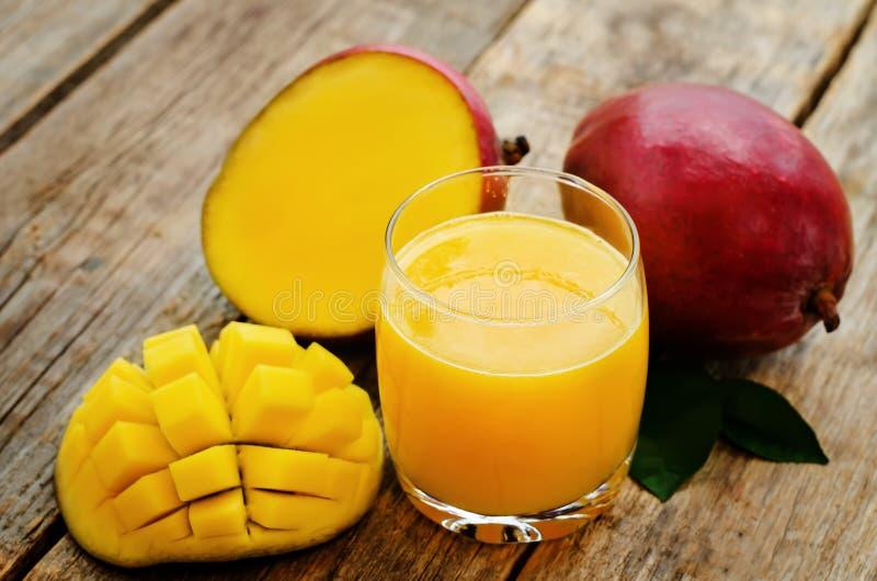 Mangofruktsaft och ny mango arkivfoton