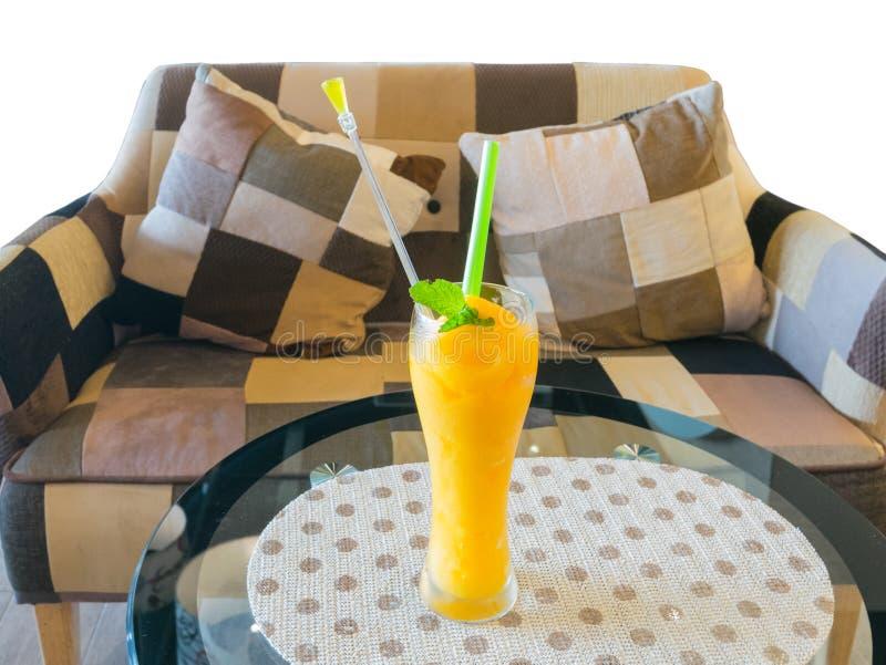Mangofruktsaft på tabellen med den bruna soffan (med den snabba banan) royaltyfria foton
