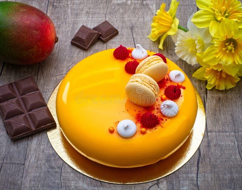 Mangokaka med choklad-, mango- och för passionfrukt mousse, med det frasiga mandellagret royaltyfri bild