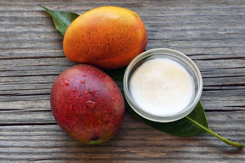 Mangokroppsmör i en exponeringsglasbunke och nya mogna organiska mangofrukter på gammal träbakgrund Spa naturliga oljor, organisk arkivbild
