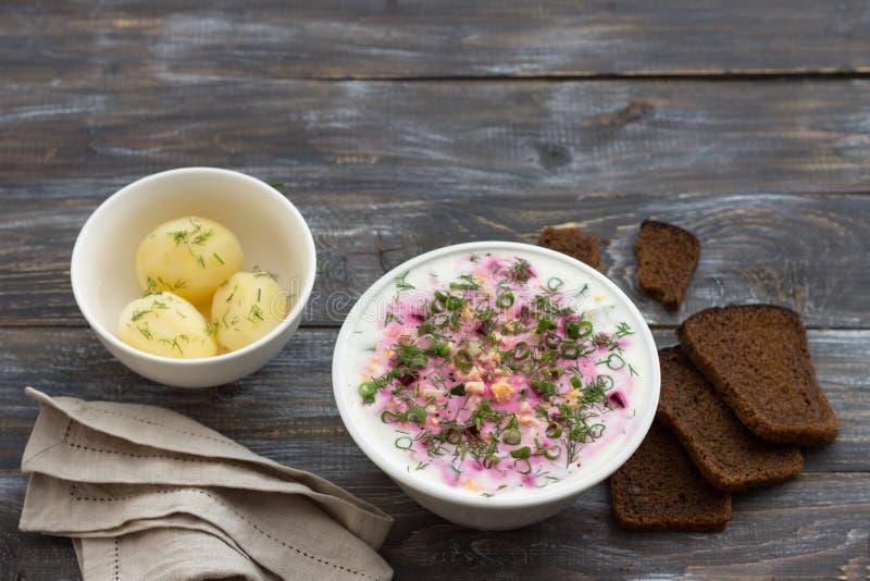 Mangoldsuppe, svekolnik, holodnik, auf Kefir, mit Gurke, gekochten Eiern und Grüns auf einem Holztisch stockbild