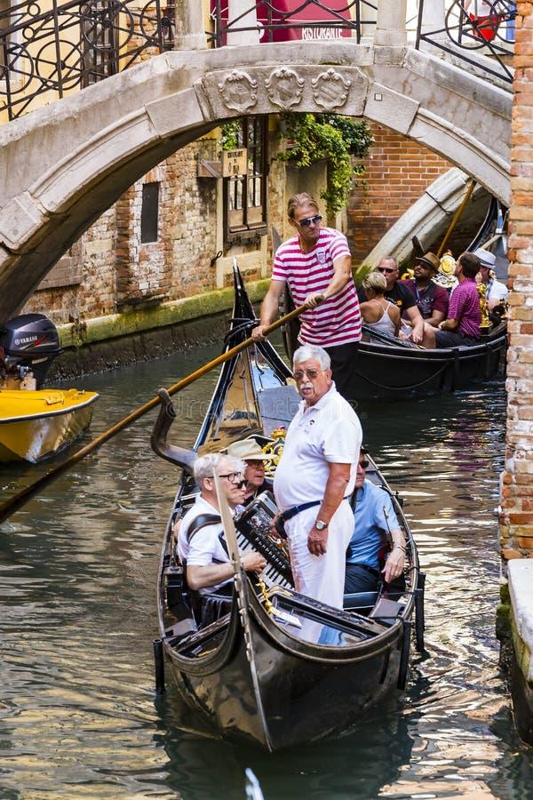 Mangondolj?rer k?r gondoler med turister i Venedig i Italien royaltyfria bilder
