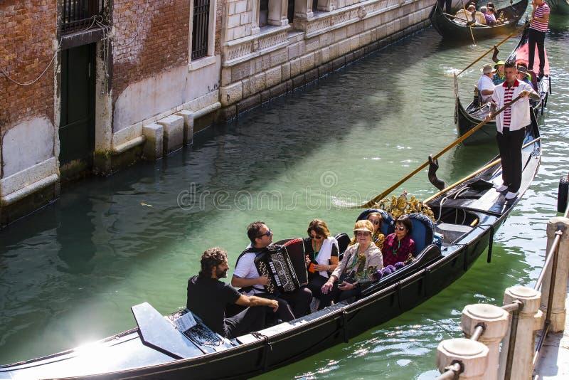 Mangondolj?rer k?r gondoler med turister i Venedig i Italien arkivfoto