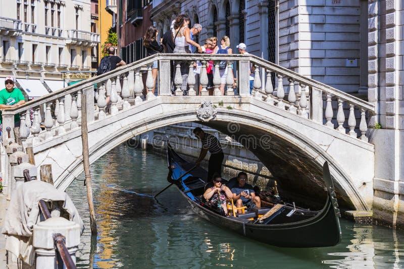 Mangondolj?rer k?r gondoler med turister i Venedig i Italien arkivbild