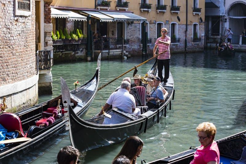 Mangondolj?rer k?r gondoler med turister i Venedig i Italien fotografering för bildbyråer