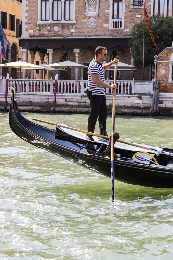 Mangondolj?rer k?r gondoler med turister i Venedig i Italien royaltyfri fotografi