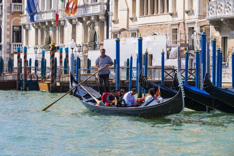 Mangondolj?rer k?r gondoler med turister i Venedig i Italien royaltyfri bild