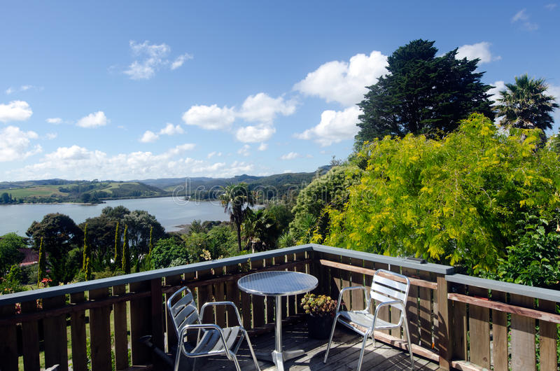 Mangonui - Northland New Zealand NZ. Two metal chairs and a table on balcony with landscape view at the background of Mangonui harbor at Doubtless Bay in stock image