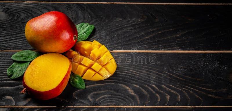 mangopflaume Tropische Früchte auf einem schwarzen hölzernen Hintergrund, Kopienraumtext, löschen für Text, Draufsicht lizenzfreie stockbilder