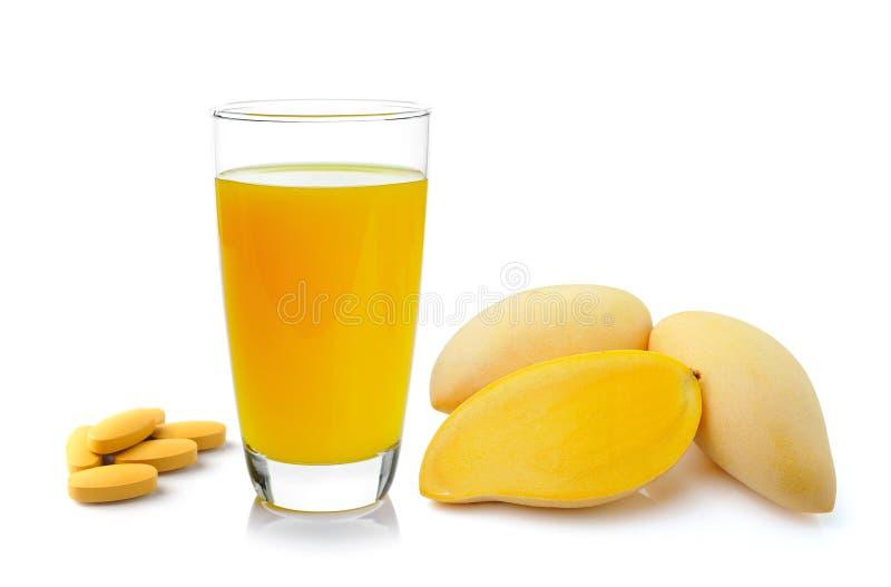 Mangosap in een glas en vitamine Ctablet op witte achtergrond stock afbeelding