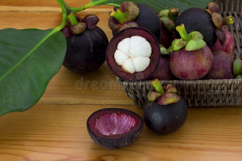 Mangostana mûr de Garcinia de mangoustans avec les feuilles vertes dans un panier sur la table en bois photos libres de droits