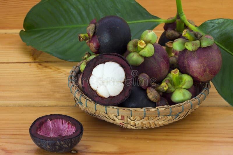 Mangostana mûr de Garcinia de mangoustans avec les feuilles vertes dans un panier sur la table en bois photo libre de droits
