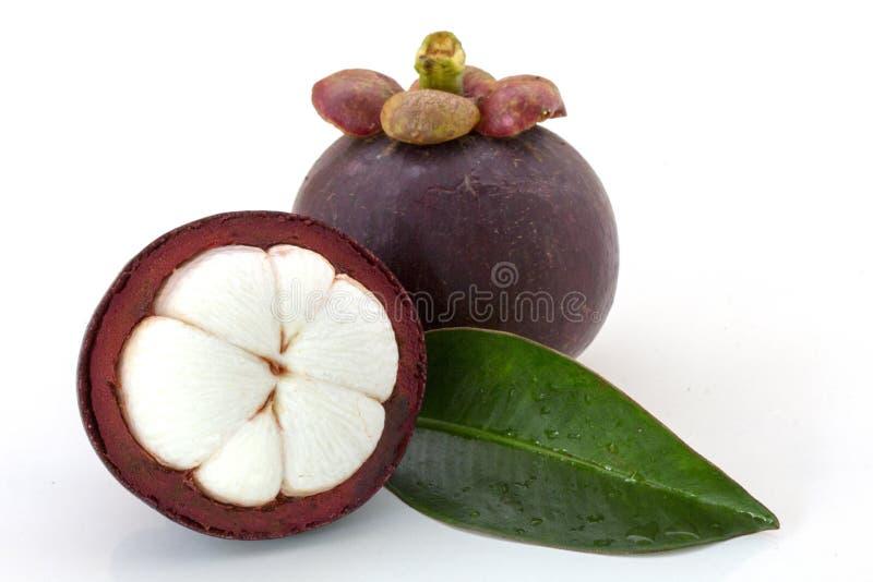 Mangostana mûr de Garcinia de mangoustans ou demi mangoustan avec les feuilles vertes d'isolement sur le fond blanc photographie stock libre de droits