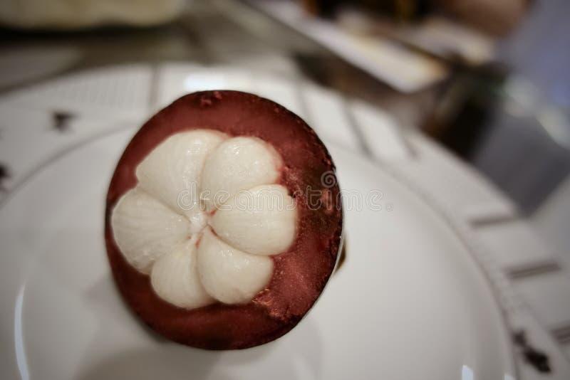 Mangostano e sezione trasversale che mostrano la carne porpora spessa di bianco e della pelle della regina dei frutti immagini stock