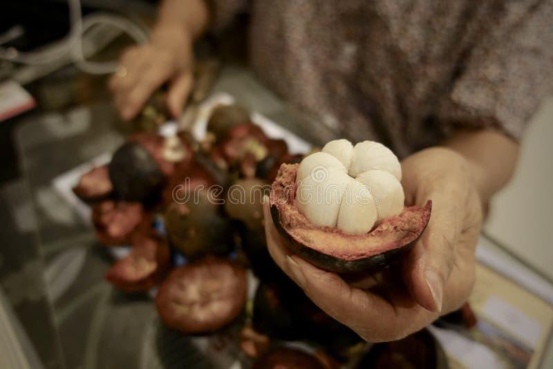 Mangoustan et section transversale montrant la chair pourpre épaisse de peau et de blanc de la reine des fruits photographie stock