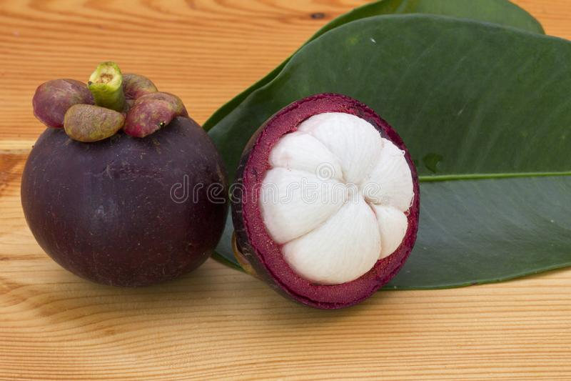 Mangoustans mûrs ou demi mangoustan avec les feuilles vertes sur une table en bois image stock