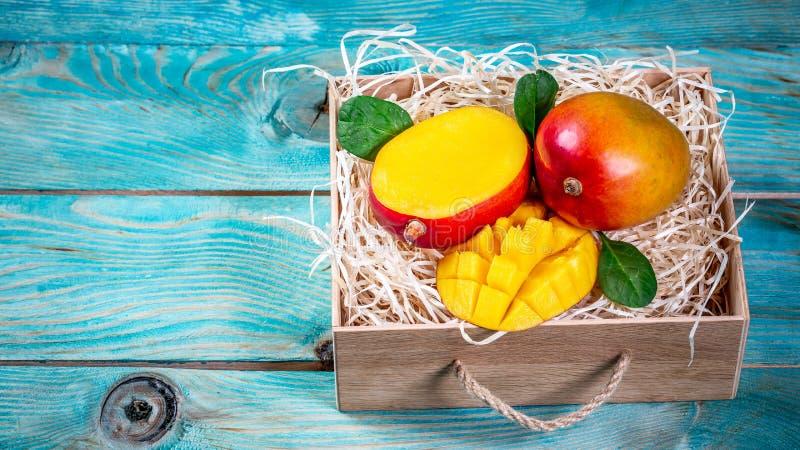 Mangovruchten in houten doos met blad na oogst van landbouwbedrijf, Mangovruchten met blad op blauwe houten achtergrond Hoogste m stock foto's