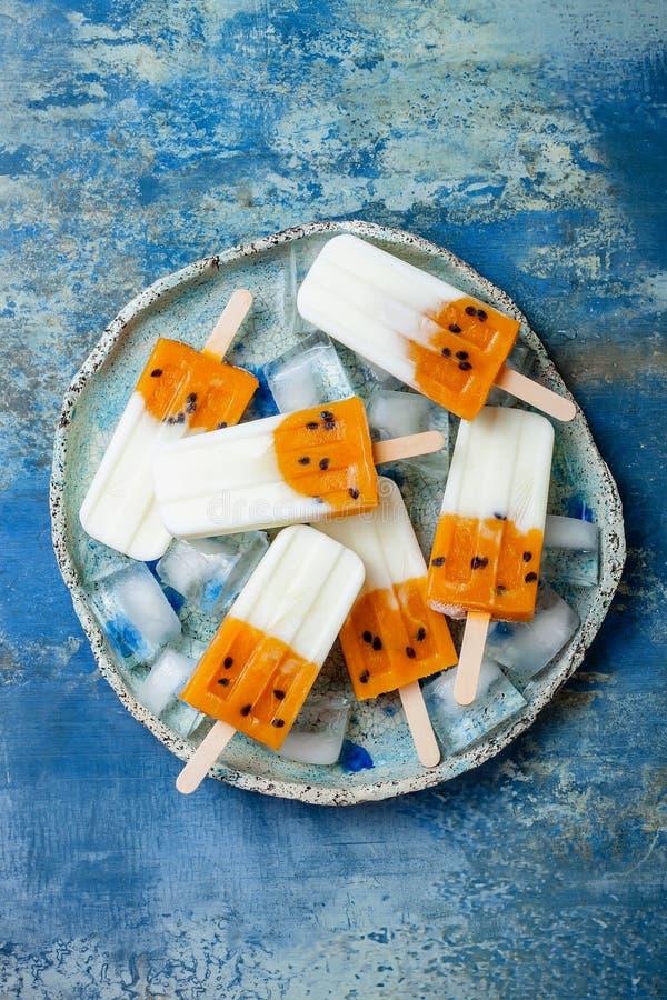 Mangowi pasyjnej owoc popsicles z kokosową śmietanką na kostka lodu nad błękita talerzem zdjęcie royalty free