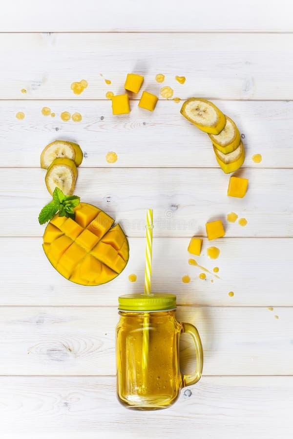 Mangowy i bananowy smoothie w kamieniarza słoju z słomą obrazy royalty free