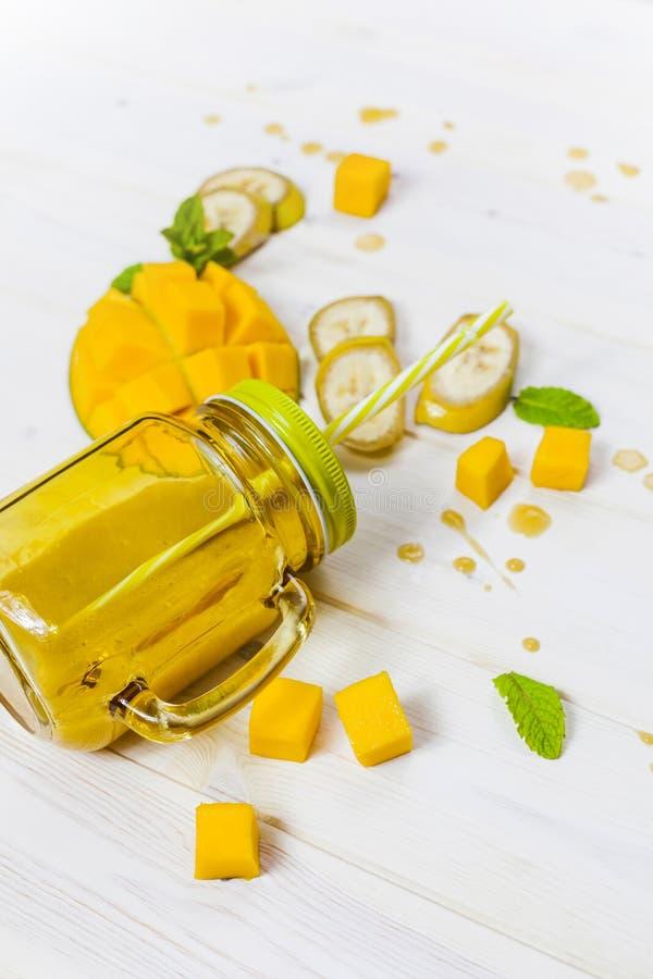 Mangowy i bananowy smoothie w kamieniarza słoju z słomą fotografia royalty free