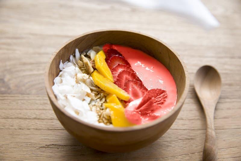 Mangowy smoothie puchar z świeżą owoc i truskawką na drewnianym tle fotografia stock