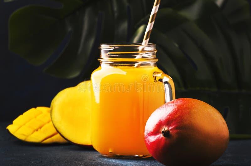 Mangowy sok lub koktajl w szklanym słoju z świeżą owoc na błękitnym tropikalnym tle, kopii przestrzeń, selekcyjna ostrość obrazy royalty free