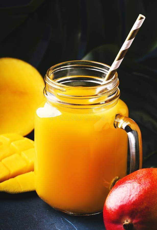 Mangowy sok lub koktajl w szklanym słoju z świeżą owoc na błękitnym tropikalnym tle, kopii przestrzeń, selekcyjna ostrość obraz stock