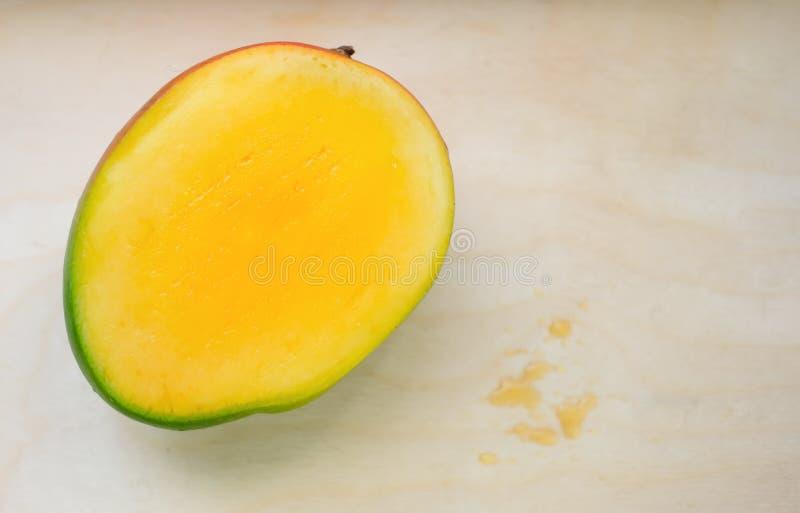Mangue exotique jaune mûre coupée en tranches sur le fond en bois avec des baisses de jus Délicatesse tropicale complètement des  photos libres de droits