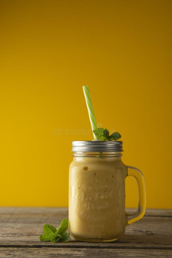 Mangue, glace de citron ou lait de poule faite maison dans des tasses de pot de maçon, fond en bois rustique Type de cru photo libre de droits