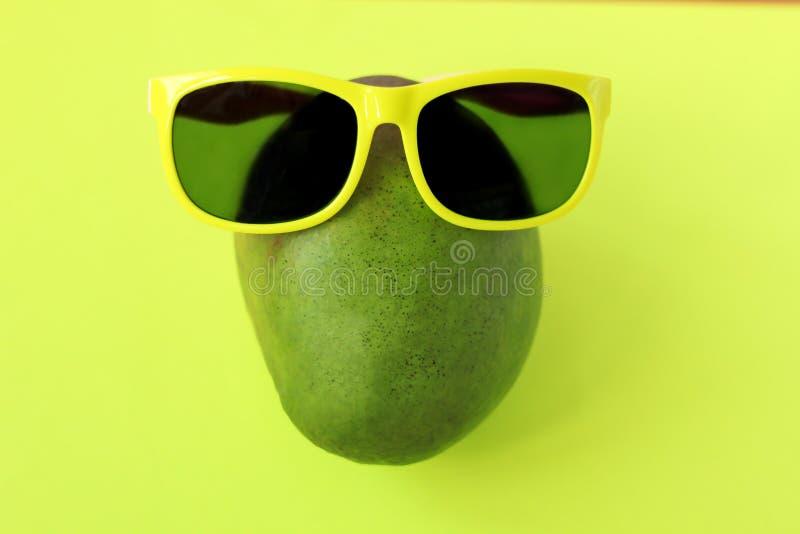 Mangue verte et rouge juteuse mûre dans des lunettes de soleil sur le fond jaune en pastel Copiez l'espace Style de Minimalistic photo libre de droits