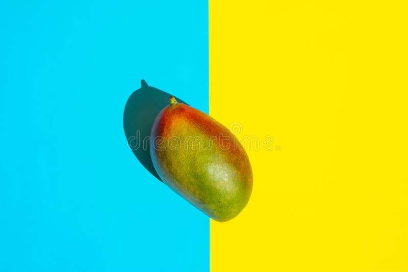 Mangue verte et rouge mûre sur le fond bleu jaune de Duotone de fente Image créative dénommée Ombres profondes de lumière du sole photo stock