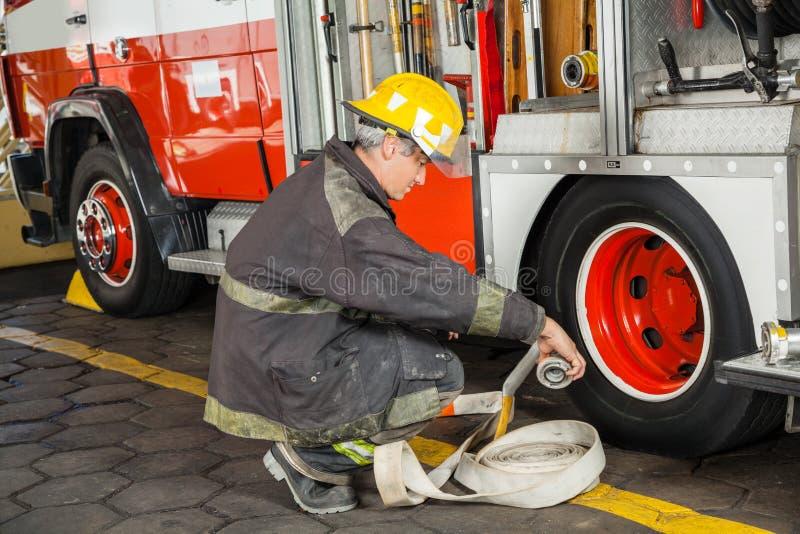 Mangueira de Crouching While Holding do sapador-bombeiro pelo caminhão imagem de stock royalty free