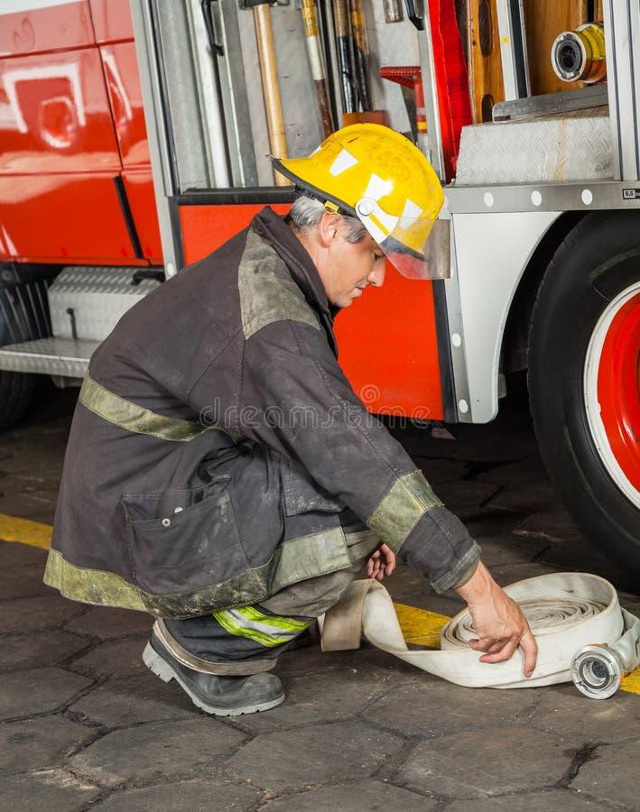 Manguera de Crouching While Holding del bombero en el fuego imagenes de archivo