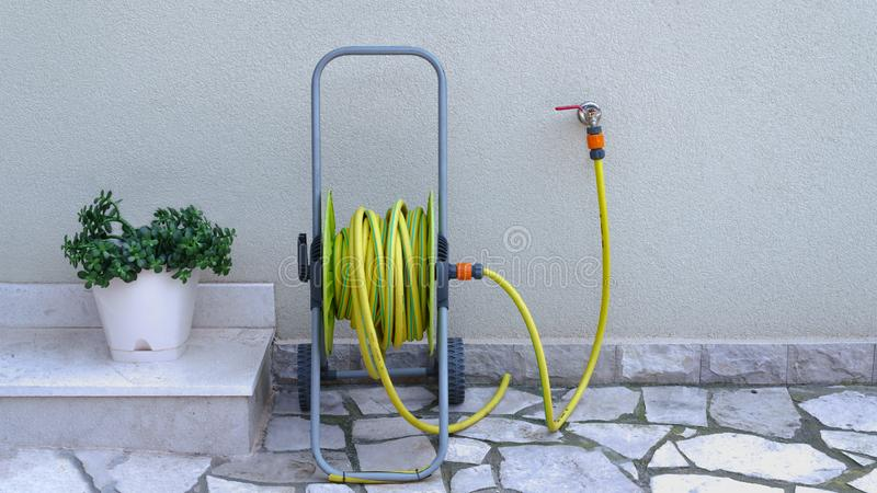 Manguera de jardín para la irrigación cerca de la pared de la casa fotos de archivo