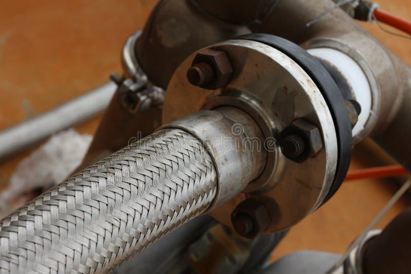 Manguera flexible con la línea de la tubería de acero fotos de archivo