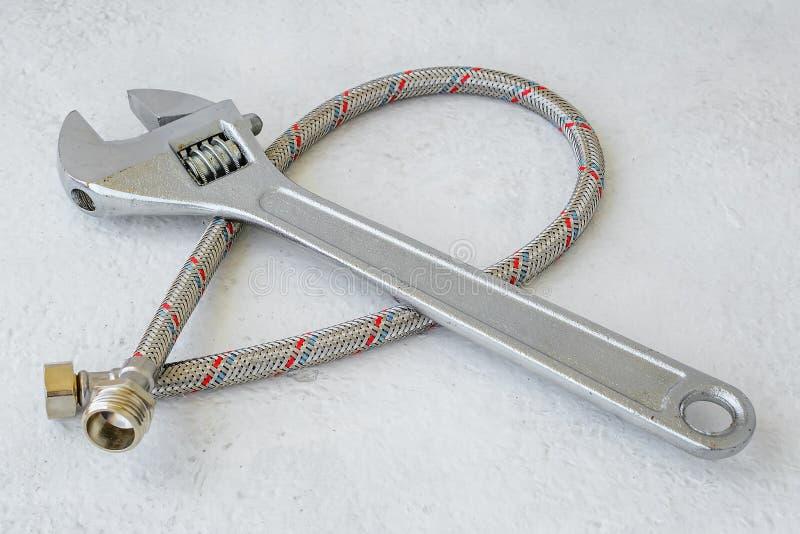 Manguera trenzada del metal flexible para sondear golpecitos y la llave ajustable del metal en un fondo blanco Herramientas de la fotos de archivo libres de regalías