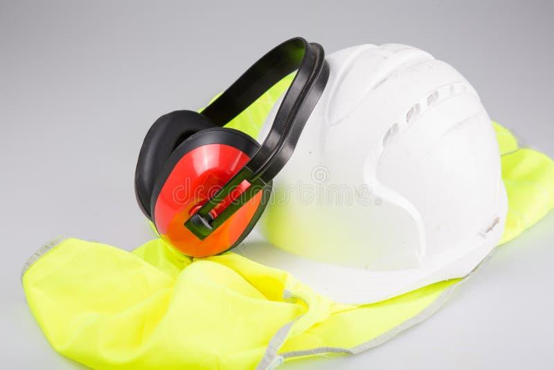 Manguitos del oído del casco colocados en el chaleco amarillo con reflexivo en el fondo blanco en concepto del trabajo de la segu foto de archivo