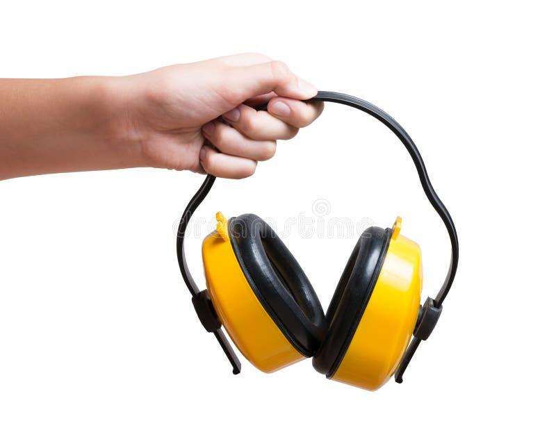 Manguitos protectores amarillos del oído a disposición aislados en un blanco imágenes de archivo libres de regalías