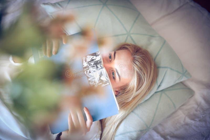 A manhã é boa hora para o estudo Estudante novo que aprende na cama imagens de stock
