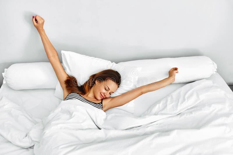 A manhã acorda Mulher que acorda o esticão na cama Estilo de vida saudável imagem de stock