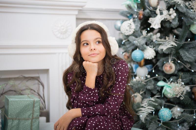 manhã antes do Xmas Feriado do ano novo Ano novo feliz menina sonhadora pequena no Natal fones de ouvido mornos Natal miúdo foto de stock