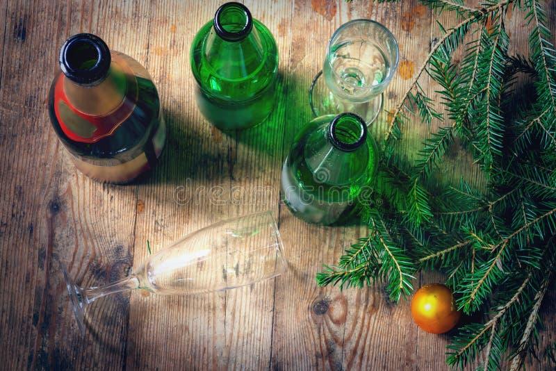 Manhã após a celebração do ano novo Diversas garrafas vazias do álcool, ramos do abeto, vidros no sujo imagem de stock