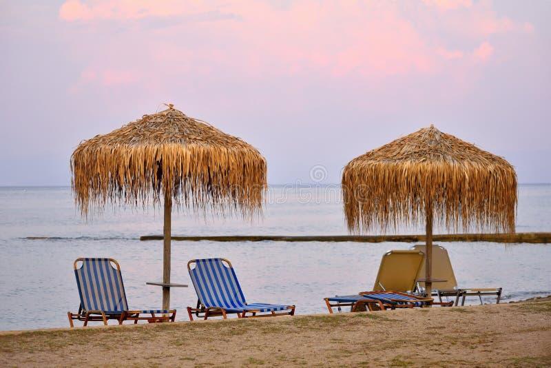 Manhã bonita - por do sol e parasóis e cadeiras de plataforma na praia pelo mar fotos de stock