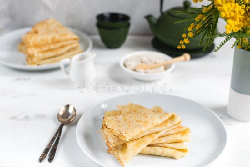 Manhã, café da manhã - panquecas tradicionais do blini do russo, crepes franceses chantiliy, bule verde do ferro fundido, flor fotografia de stock royalty free