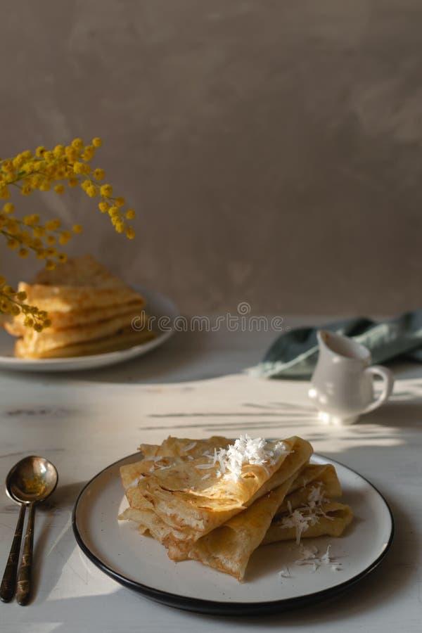 Manhã, café da manhã - panquecas tradicionais do blini do russo, crepes franceses chantiliy, flor da mimosa foto de stock royalty free