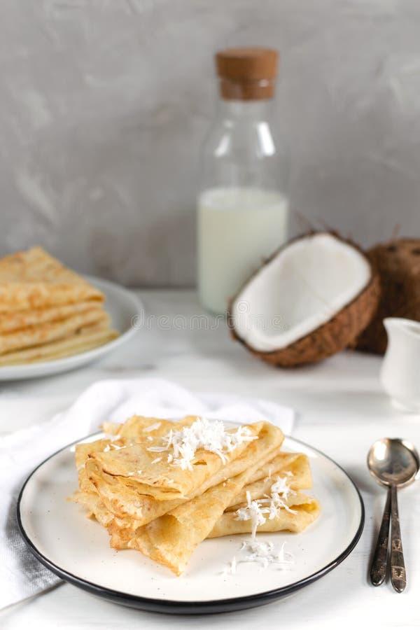 Manhã, café da manhã - panquecas tradicionais do blini do russo, crepes franceses, coco fresco, garrafa de leite, jarro cerâm fotos de stock