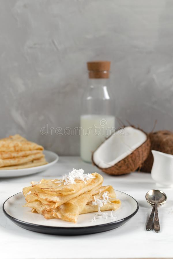 Manhã, café da manhã - panquecas tradicionais do blini do russo, crepes franceses, coco fresco, garrafa de leite, jarro cerâm foto de stock