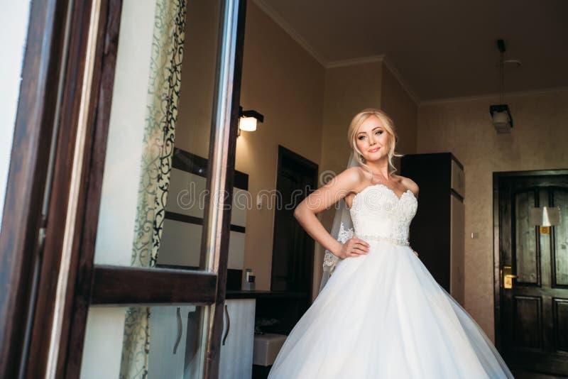 Manhã da mulher bonita Dia do casamento Noiva bonita Vestido de casamento Noiva vestida no hotel imagens de stock