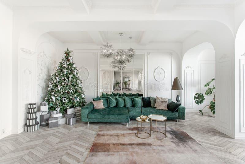 Manhã de Natal apartamentos luxuosos clássicos com a árvore de Natal decorada Grande espelho de vida do salão, sofá verde imagens de stock