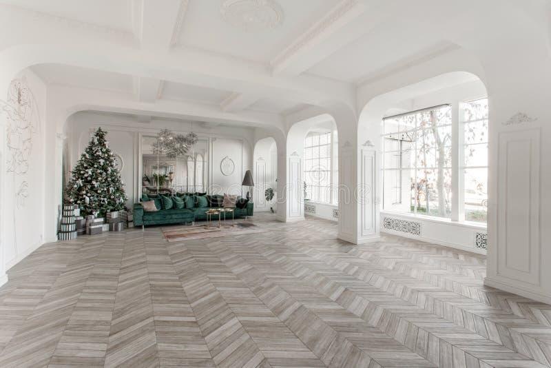 Manhã de Natal apartamentos luxuosos clássicos com a árvore de Natal decorada Grande espelho de vida do salão, sofá verde fotos de stock